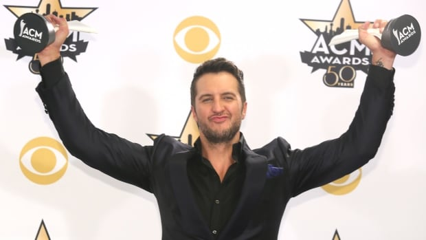 Luke Bryan poses in the press room with the awards for entertainer of the year and vocal event of the year at the 50th annual Academy of Country Music Awards on Sunday at AT&T Stadium in Arlington, Texas.