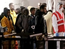 Migrants rest after they disembarked in the Sicilian harbour of Augusta. Italian police arrested 15 African men suspected of throwing about a dozen Christians from a migrant boat in the Mediterranean, as the crisis off southern Italy intensified.
