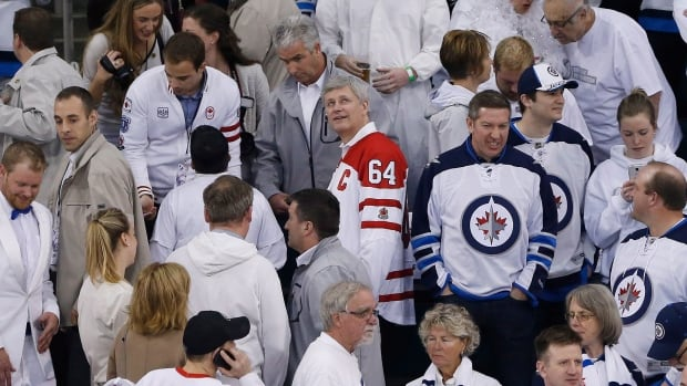 Prime Minister Stephen Harper looks up at the score board prior to the puck drop in Game 4 of the NHL playoffs' first series between the Winnipeg Jets and the Anaheim Ducks at the MTS Centre on Wednesday, April 22, 2015. He's still in the city today appearing at three different locations.