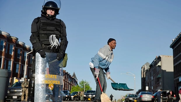 Baltimore residents clean their streets as law enforcement officers and Maryland's National Guard patrol in the aftermath of Monday's rioting.