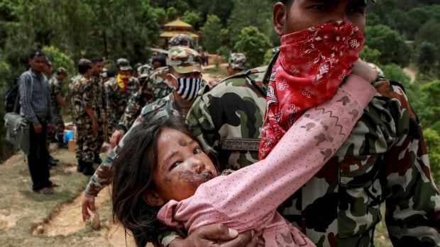 An injured girl is carried by a Nepal Army personnel to a helicopter following Saturday's earthquake in Sindhupalchowk, Nepal, April 28, 2015.