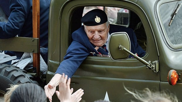 Young Dutch children reach out to the hand of a Second World War veteran as he takes part in the parade to celebrate the 70th anniversary of the Liberation of the Netherlands in Wageningen, Netherlands on Tuesday, May 5, 2015. The Apeldoorn parade, a special thanks to Canada, is Saturday.