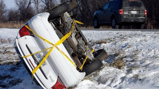 A car rests on its side in the centre of Highway 401 near Rodney, Ont., about 75 km west of London in 2008. The Ontario government's proposed changes to auto insurance would mean people suffering from serious car injuries are worse off, critics say.