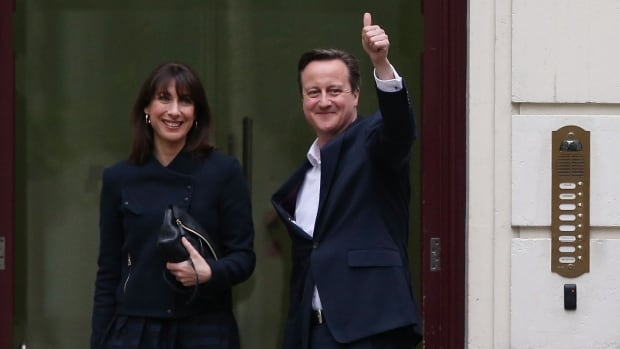 Prime Minister David Cameron arrives in London with his wife Samantha early Friday after his party defied pre-election polls and won a majority of the seats in parliament.