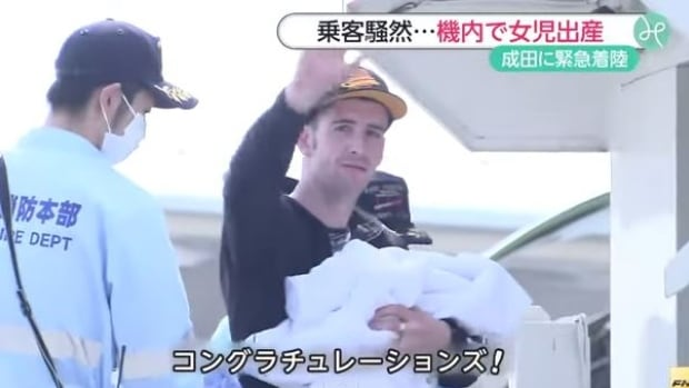 The father of a baby born on a flight from Calgary to Tokyo holds his newborn daughter and waves to reporters on the tarmac.