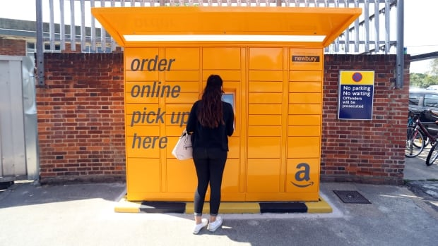 Canada Post says more than three quarters of Canadians bought something online last year, like this woman using an automated Amazon.com kiosk is doing.