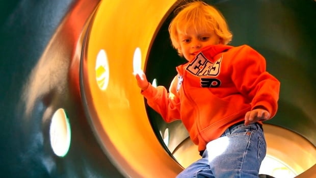 Michael Hoffman, 3, of Newtown, Pa., climbs through a tunnel at a playground.