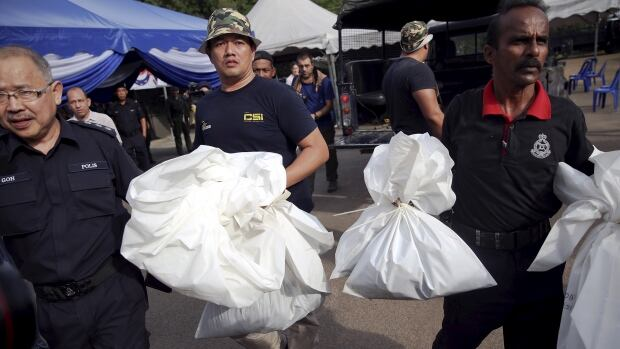 Malaysian forensic policemen on Monday carry body bags with human remains found at the site of human trafficking camps in the jungle near the Thailand border.