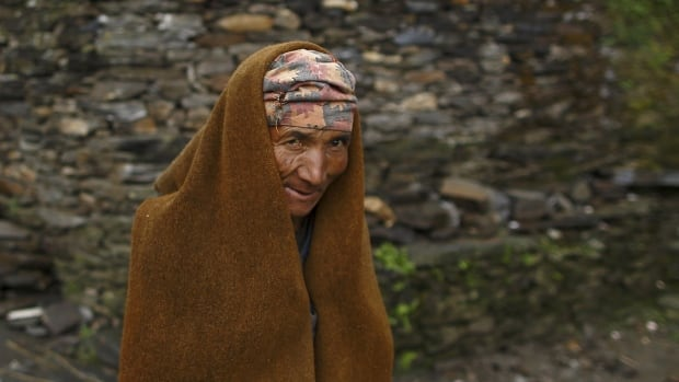 Tes Bahadur Ghale, 60, an earthquake victim covers himself with a cloth made up of sheep wool as he walks towards his collapsed house in Gorkha district, Nepal. The priority now is to find temporary housing for people before the monsoon rains start.