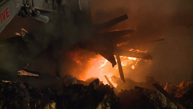 An excavator works through the burning rubble, allowing firefighters to access the hot spots, more than six hours after the fire began at Mattress Recycling.