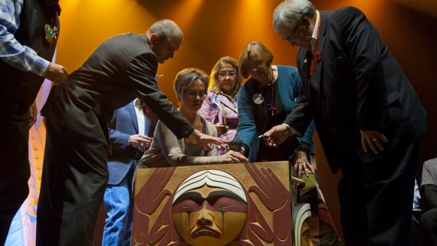 TRC commissioners join United Church officials to place an expression of reconciliation in the bentwood box.
