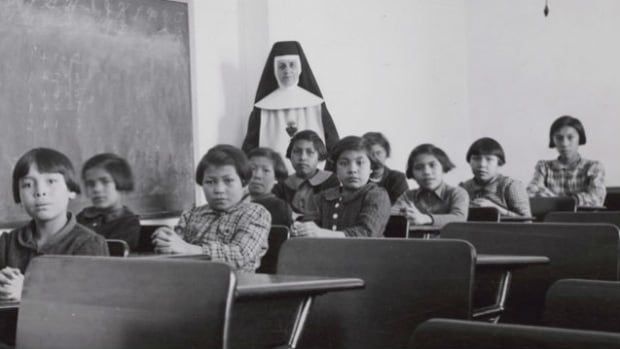 A group of female students and a nun pose in a classroom at Cross Lake Indian Residential School in Cross Lake, Man., in a February 1940 archive photo.