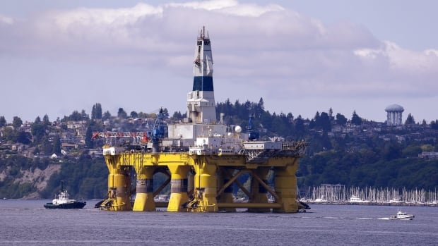 The oil drilling rig Polar Pioneer is towed toward a dock in Seattle, on its way to explore for oil off Alaska's northwest shore this summer. Environmental groups say that an environmental analysis before the oil leases were sold to Shell ignored walrus habitat and the impact on climate.