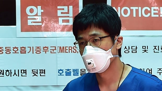 A South Korean hospital worker wears a mask in front of a public notice on MERS while setting up a separated emergency centre in Seoul. International surveillance for cases remains essential, public health authorities say.