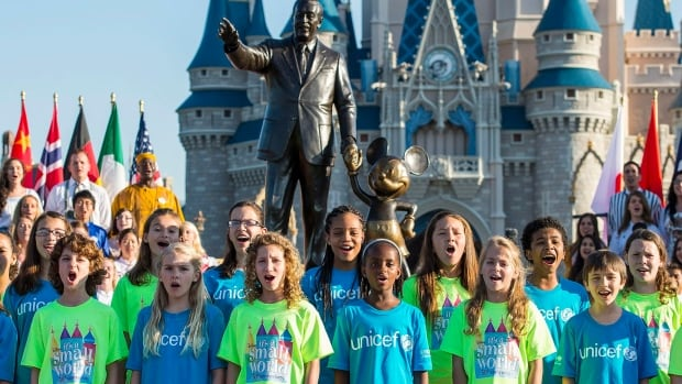 A children's chorus sings It's a Small World at Walt Disney World in Florida. Behind the scenes, Disney laid off its IT workers so it could hire foreign employees on H-1B visas.