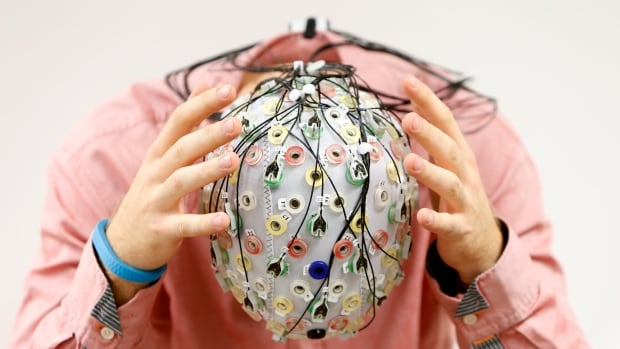 A test subject poses with an electroencephalography cap, which measures brain activity.