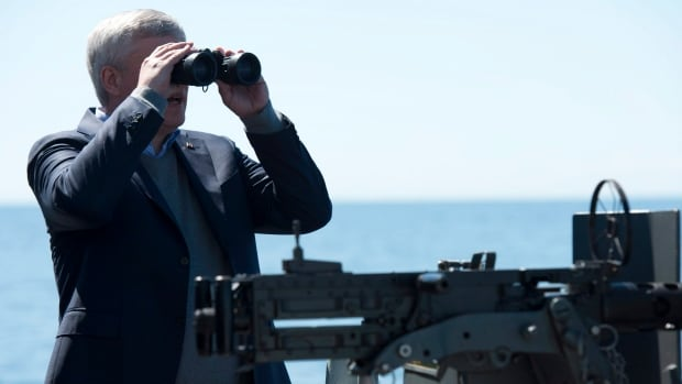 Prime Minister Stephen Harper uses binoculars to look at ships on the horizon as HMCS Fredericton sails in the Baltic Sea on Wednesday.