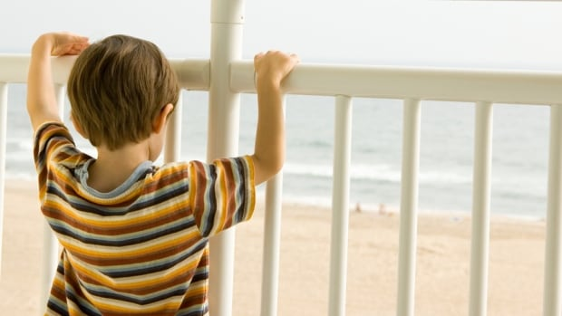 A child looks out at the ocean from a balcony. BC Children's Hospital says it has seen a spike in children falling from balconies and windows in the warm weather.