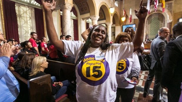 Workers react as the Los Angeles City Council approved a $15 minimum wage by a 13-1 margin in June. On Wednesday, the hike passed a final vote.