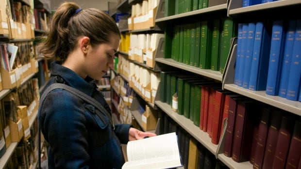 A student leafs through bound journals at a library at the University of Toronto.  A new study shows that the five largest, for-profit academic publishers now publish 53 per cent of scientific papers in the natural and medical sciences – up from 20 per cent in 1973.