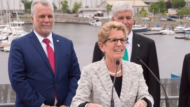 Ontario Premier Kathleen Wynne, centre, is meeting with Quebec Premier Philippe Couillard, left, Michigan Gov. Rick Snyder and the leaders of 7 other states in Quebec City. She invited her American peers to join a headline-grabbing anti-emissions pact between Ontario, Quebec and California.