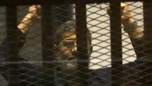 Egypt's ousted Islamist President Mohammed Morsi gestures in a defendant's cage at the Police Academy courthouse in Cairo, Egypt, Tuesday. An Egyptian court a confirmed a death sentence handed to Morsi over a mass prison break during the 2011 uprising.