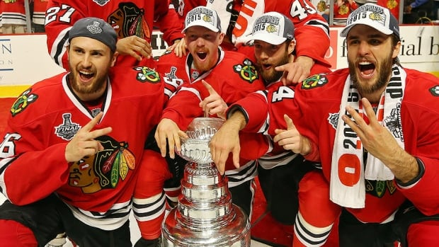 The Blackhawks pose with the Stanley Cup after defeating Tampa Bay  2-0 in Game 6 Monday night in Chicago. With their third championship in six years, the Blackhawks are drawing comparisons to the Montreal Canadiens of the 1970s and New York Islanders of the '80s, teams that won four consecutive titles. Are these Hawks a dynasty or, perhaps, a redefined dynasty, given the NHL now operates under a salary cap?