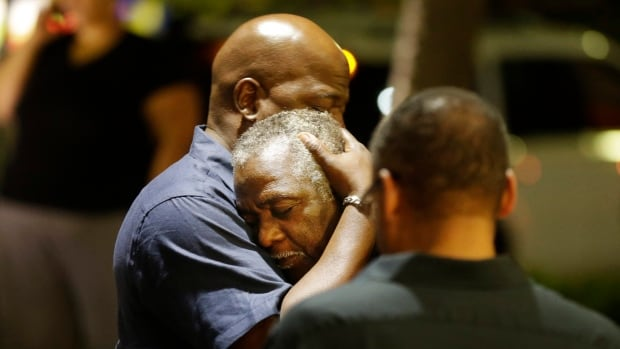 Worshippers embrace following a group prayer across the street from the scene of the shooting on Wednesday.