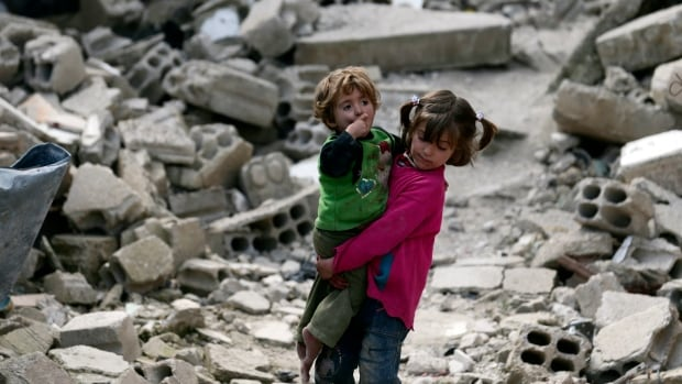 Local resident Israa holds her sister Boutol as they make their way through rubble of damaged buildings in the Douma neighborhood of Damascus March 4, 2015.