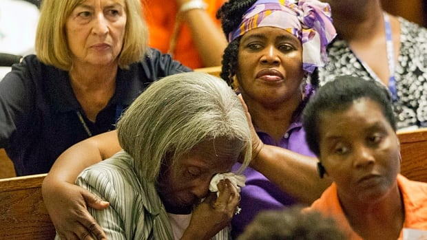 Parishioners comfort one another during a memorial service for the people killed Wednesday during a prayer meeting inside the historic black church in Charleston, S.C.