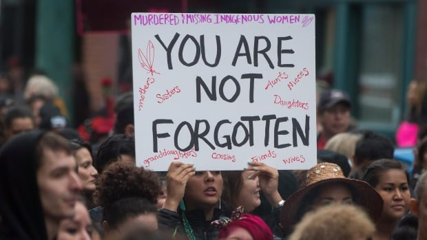 A woman holds a sign as hundreds of people march through the Downtown Eastside during the 25th annual Women's Memorial March in Vancouver, B.C., on Saturday February 14, 2015. The march is held to honour missing and murdered women and girls from the community with stops along the way to commemorate where women were last seen or found.