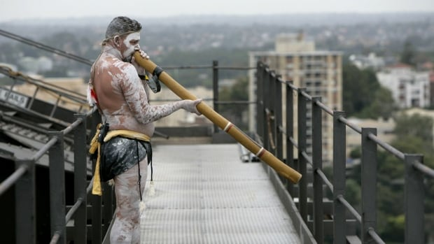 Aboriginal artist Mathew Doyle plays the didgeridoo to signal the start of celebrations to commemorate the 75th anniversary of the Sydney Harbor Bridge, in Australia. The didgeridoo will become the official sound for Port Alberni's tsunami warning system.