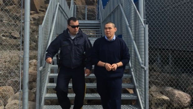 Peter Kingwatsiak leaves the Iqaluit courthouse last June during his murder trial, flanked by a police officer.