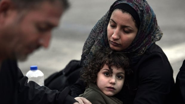 A Syrian mother tries to warm up her daugter after they arrived on the  island of Lesbos, early on June 18, 2015. Some 48,000 migrants and refugees have landed on Greek shores so far this year, compared to 34,000 arrivals during all of 2014, according to the International Organization for Migration (IOM).