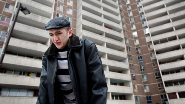 In this 2010 photo, Uzbek refugee Dilshod Marupov stands in front of a Toronto apartment building where he was almost killed in a scaffold collapse the year before.