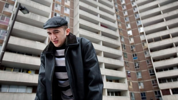 Dilshod Marupov, 22, stands in front of a Toronto apartment building in 2010 where he was almost killed in an industrial accident; four others died. The crew's supervisor will be sentenced in the case Monday.