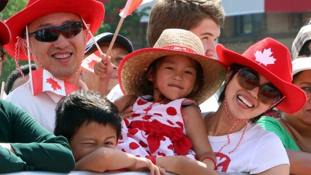 Ron Liu, along with his six-year-old son Robbie, four-year-old daughter Elaine and his wife May (left to right), take part in Canada Day celebrations on Parliament Hill in 2014.