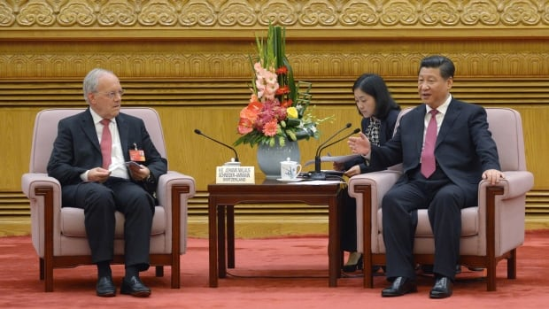 Chinese President Xi Jinping, right, speaks to Swiss economy minister Johann Schneider-Ammann as he meets with delegates attending the signing ceremony for the Articles of Agreement of the Asian Infrastructure Investment Bank at the Great Hall of the People in Beijing on Monday.