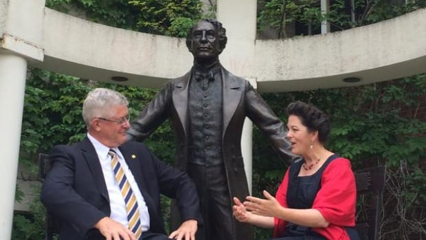Wilfrid Laurier president Max Blouw and sculptor Ruth Abernethy sit with the Sir John A. Macdonald statue. Abernethy included over 30 symbols on the piece, which represent Macdonald's personal life, political triumphs and scandals.
