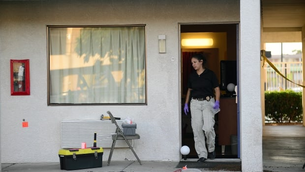 An Albuquerque Police Deptartment officer collects evidence Wednesday, July 1, 2015, after a man was killed and another injured during what police say was an altercation between the two late Tuesday at a Motel 6.
