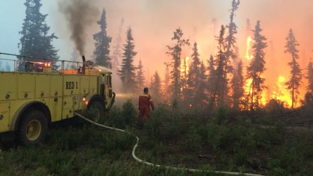 A fire fighter helps fight wildfire in the La Ronge, Sask. area, while a fire truck sprays water to dose the flames, on July 4, 2015.