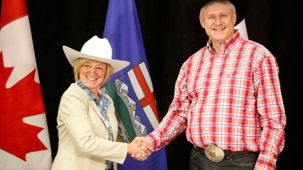 Alberta Premier Rachel Notley, left, greets Prime Minister Stephen Harper with a handshake in Calgary, Alta., on Monday.
