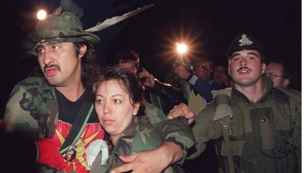 Mohawk Warrior known as Noreiga clutches a Mohawk woman as he is taken into costody Sept. 26, 1990 by Canadian soldiers during the surrender at the Kanasehtake Reserve at Oka. It was a crisis that grabbed international headlines, with armed Mohawks and Canadian soldiers involved in a lengthy standoff that often appeared on the verge of exploding into full-blown combat.