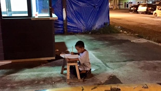 Joyce Torrefrance posted this photo of Daniel Cabrera, 9, doing his homework outside a McDonald's in the Philippines. It spurred others to raise money to fund his education, and send him school supplies and uniforms.