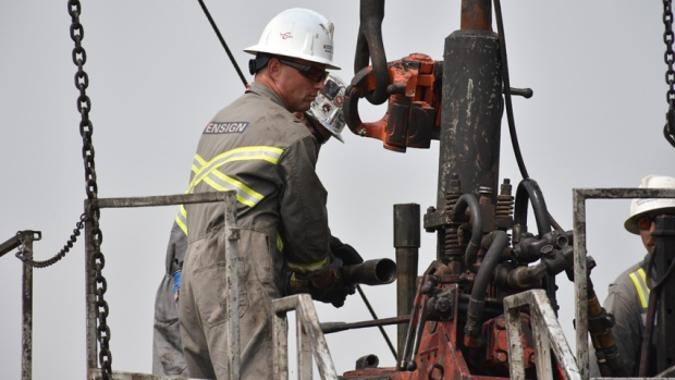 A worker with Ensign Energy pulls sections of pipe out of the ground at an orphan well site near Sunnynook, Alta.