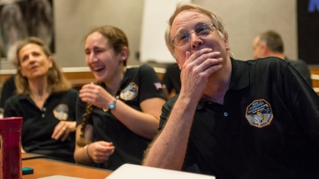 Members of the New Horizons science team reacttoseeing thespacecraft'slast and sharpestimage of Pluto.