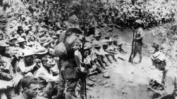 In this 1942 file photo provided by the U.S. Marine Corps, Japanese soldiers stand guard over American prisoners of war just before the start of the Bataan Death March following the Japanese occupation of the Philippines.