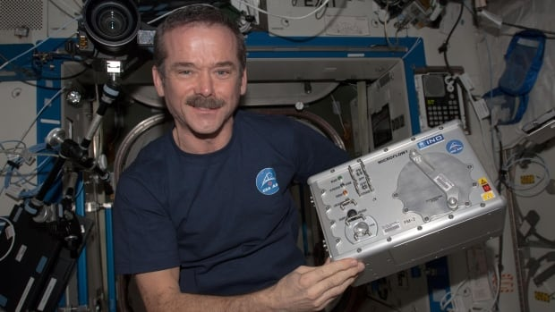 Canadian Space Agency astronaut Chris Hadfield holds the Microflow experiment to test how the instrument counts blood cells in orbit. Such space spinoffs have the potential to be applied to outbreaks of infectious diseases on Earth.