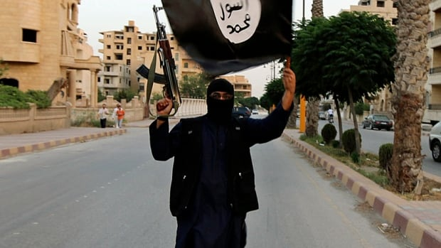A fighter waves an ISIS flag in Raqqa in June 2014, after the town was taken over by militants. Six university students who were expelled from their homes by ISIS and threatened with death because they refused to accept its rule started the citizen journalism group Raqqa is Being Slaughtered Silently.