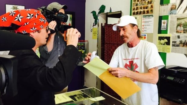 Glenn Price, right, makes his first sale at the reopening of his medical marijuana dispensary on Winnipeg's Main Street on Tuesday morning.